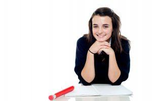 Attractive confident young schoolgirl posing in front of camera