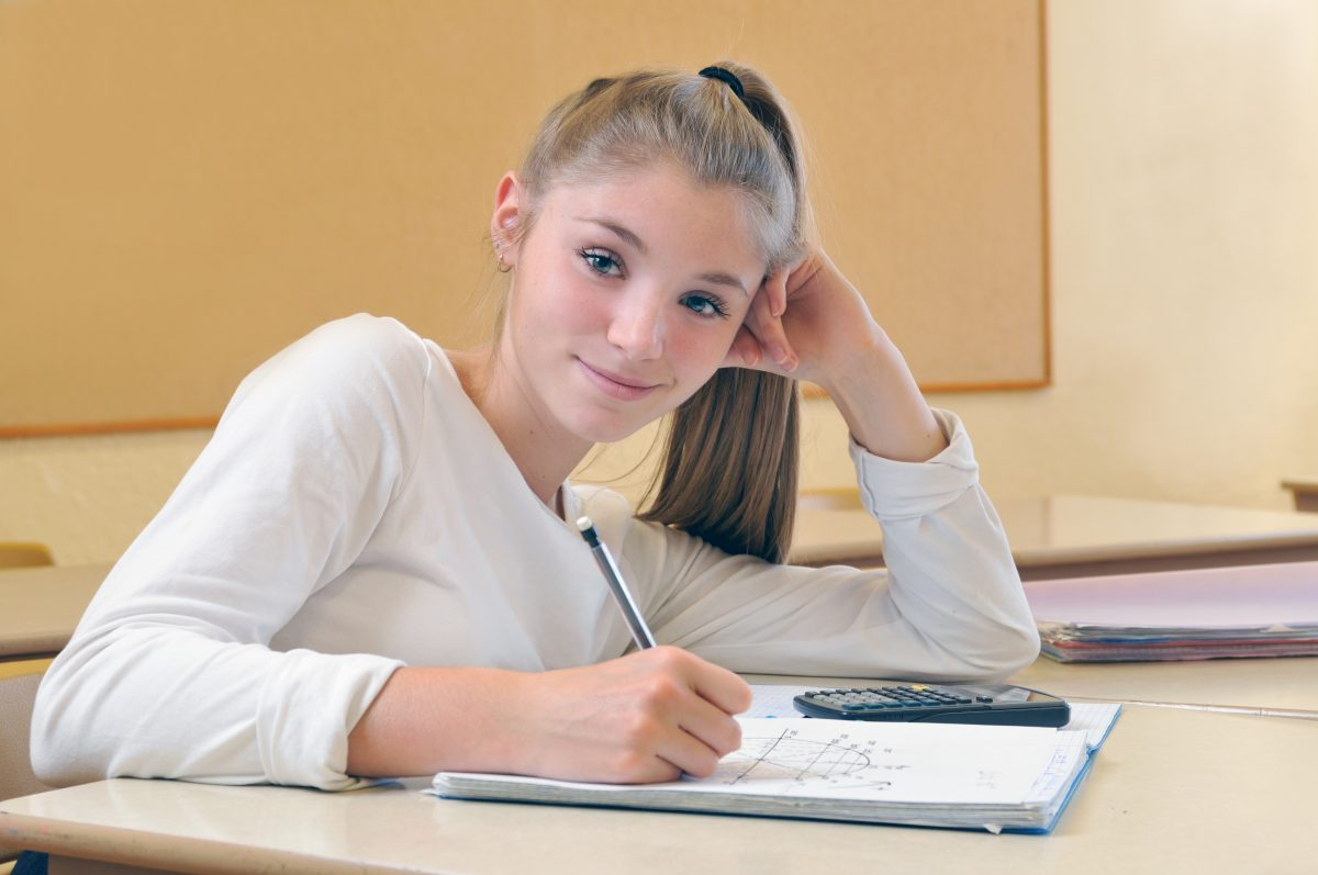 Smiling student is about a problem in math class